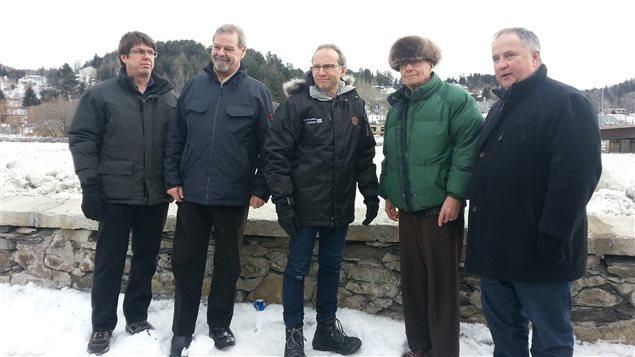 Le ministre de la Sécurité publique, Martin Coiteux, entouré des élus des régions touchées par des innondations.