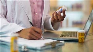 Une pharmacienne prend des notes.