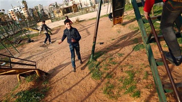 Des enfants syriens jouent au parc à Douma, un quartier contrôlé par les rebelles à Damas, le premier jour de la trêve. (27 février 2016)