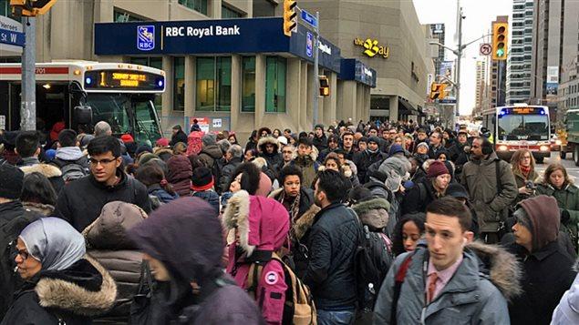 Marée humaine à l'intersection Yonge-Bloor au centre-ville de Toronto: certains usagers attendent les autobus de remplacement, d'autres choisissent de marcher.