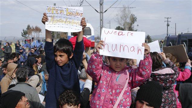 «Macédoniens, ouvrez les frontières» et «Nous sommes humains», clament ces deux enfants de migrants par l'intermédiaire de leurs affichettes.