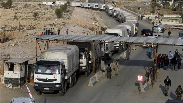 Un convoi du Croissant rouge arabe syrien arrive au camp de Wafideen, sous contrôle des forces gouvernementales, en route vers des quartiers de Douma contrôlés par les rebelles et assiégés par Damas.