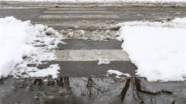 Un passage piétonnier avec de la neige fondue, de l'eau et de la glace.