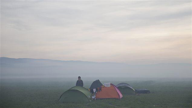 Un réfugié se tient près de sa tente, en attente de pouvoir entrer en territoire macédonien.
