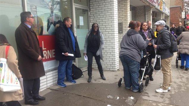 Une vingtaine de personnes manifeste devant le bureau du ministre des Finances Bill Morneau à Toronto pour la mise en place d'une stratégie nationale de logements sociaux.