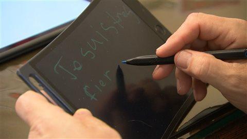Mauril Bélanger utilise une tablette pour communiquer avec ses employés.