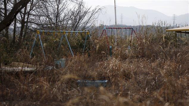 Balançoires d'une cour de garderie couvertes d'herbes dans la zone d'exclusion à Okuma, près de Fukushima, le 13 février 2016.