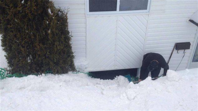 Derek Mimeault enlève la neige devant la fenêtre du sous-sol