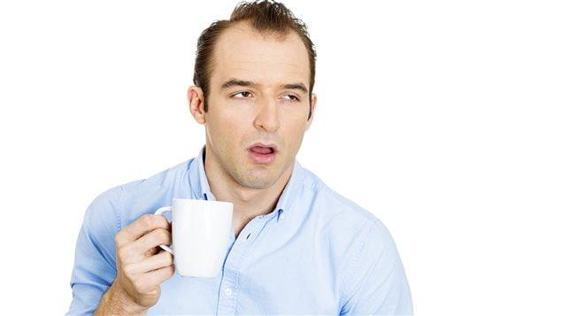 Un homme fatigué boit son café.