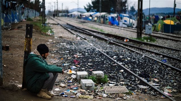 Un migrant est assis le long de la voie ferrée qui relie la Grèce et la Macédoine.