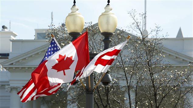 Les drapeaux du Canada et des États-Unis flottent devant la Maison-Blanche.