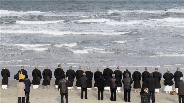 Des moines bouddhistes et des proches de victimes se recueillent lors d'une cérémonie le 11 mars 2016, à Iwaki, dans la préfecture de Fukushima.