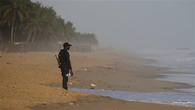 Un membre des forces de sécurité ivoiriennes fait le guet sur la plage, à la suite d'une fusillade à Grand-Bassam, en Côte d'Ivoire.