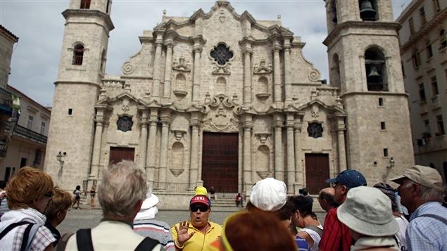 Un guide touristique et un regroupement de voyageurs sur la Plaza de la Catedral, à La Havane.