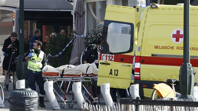 Une victime de la fusillade survenue au cours d'une perquisition à Bruxelles est évacuée en ambulance.