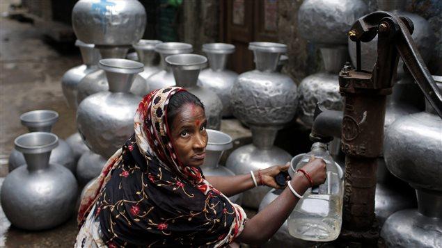 Une femme remplit une cruche d'eau à partir d'une pompe manuelle à Dhaka, au Bangladesh.