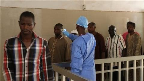 Un membre du personnel d'un hôpital de Conakry prend la température de personnes qui pourraient être infectées par le virus Ebola