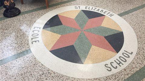 Sur le plancher du hall, une mosaïque rappelle la fonction originale de l'édifice.