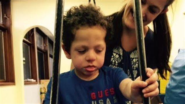 Des thérapeutes enseignent à l'enfant à utiliser un nouvel équipement pour se déplacer.