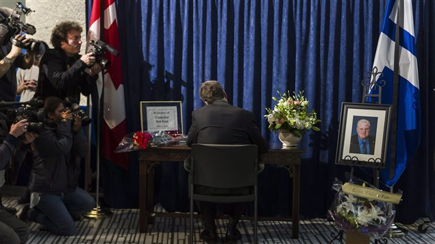 Le maire de Toronto, John Tory, signe le livre de condoléances pour Rob Ford à l'hôtel de ville.