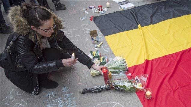 Une femme place une bougie lors de la veillée devant le Consulat général de Belgique à Montréal.