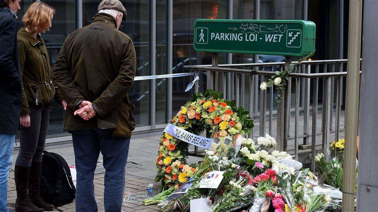 Des passants laissent des couronnes de fleurs près de la station de métro Maalbeek à Bruxelles, le 23 mars 2016. PATRIK STOLLARZ/AFP/Getty Images