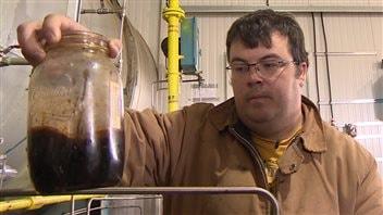 Matt Cugnet montre le pétrole qu'il vend présentement à 24$ du baril.