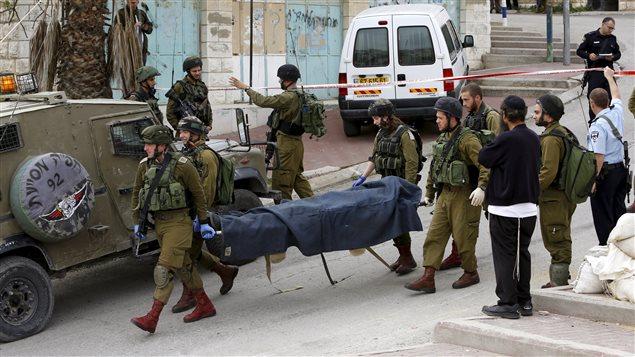 Des soldats israéliens transportent le corps d'un Palestinien abattu, à Hébron en Cisjordanie.