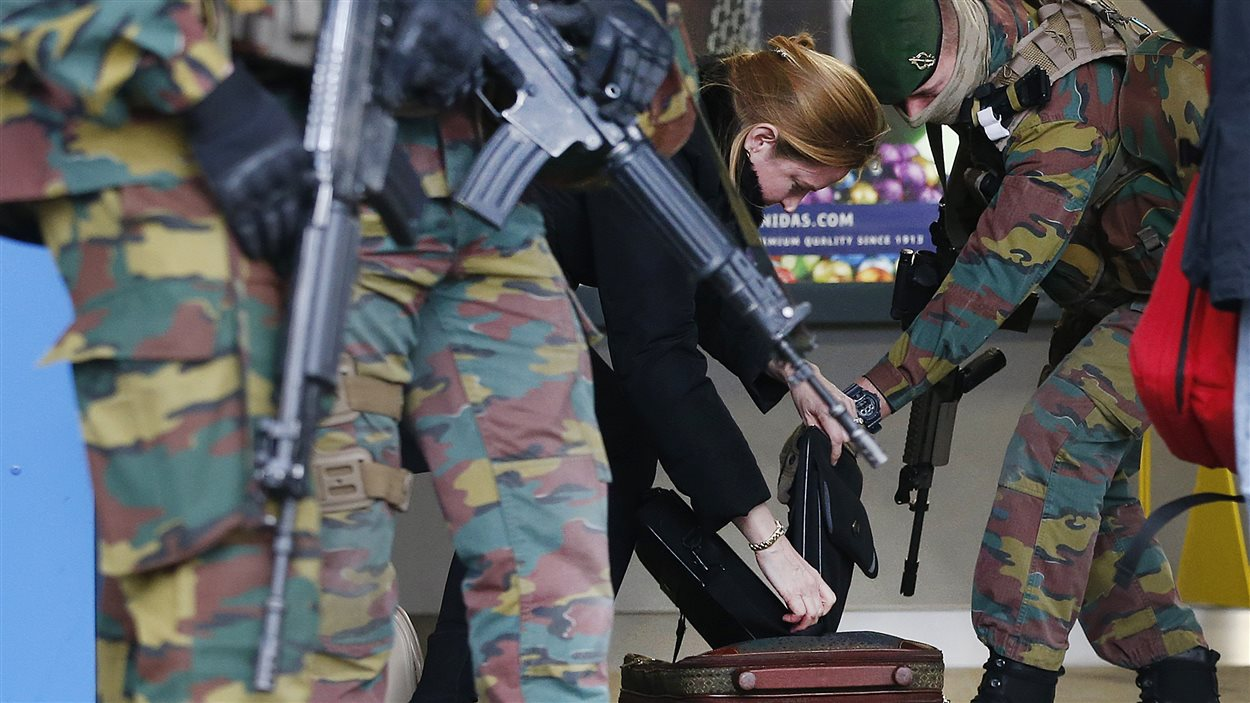 Le bagage d'une femme est fouillé par des soldats à l'entrée d'une station de métro de Bruxelles, trois jours après les attentats qui ont paralysé la capitale.