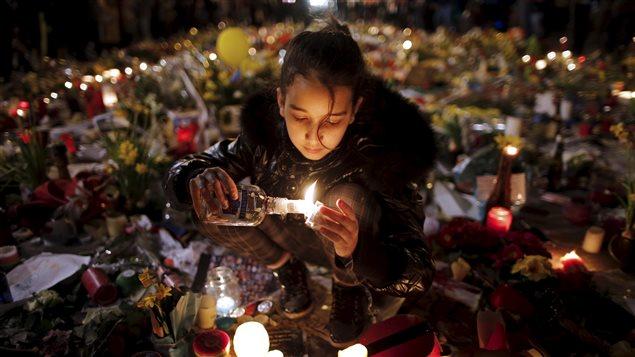 Une jeune femme allume un lampion, Place de la Bourse à Bruxelles, en hommage aux victimes.