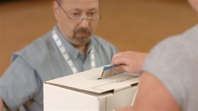 Un électeur dépose son bulletin de vote dans la boîte.