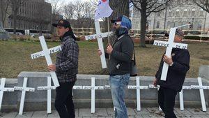 Des membres de la FTQ ont déposé des croix devant l'Assemblée nationale pour rendre hommage aux travailleurs décédés en 2015.