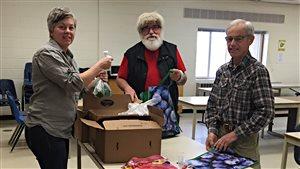 Des bénévoles placent les fruits et légumes dans des sacs.