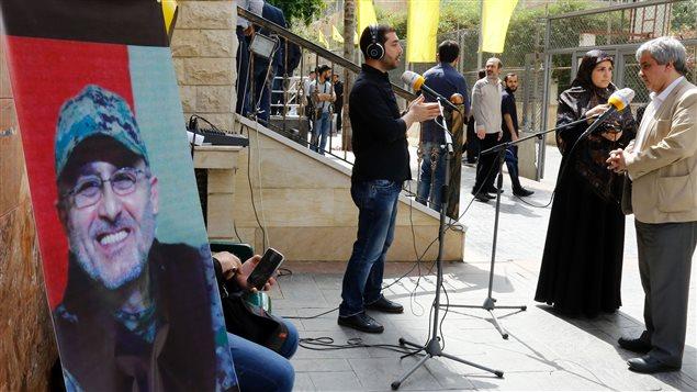 La presse libanaise s'est massée devant la résidence où la famille de Mustafa Badreddine (sur l'affiche à l'avant-plan) reçoit les condoléances.