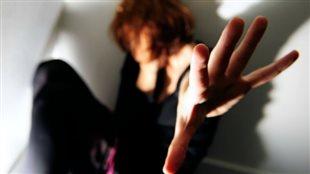 Une femme qui tend la main pour prévenir un geste de violence.