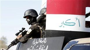 Des combattants sunnites prennent part à une parade dans le cadre de la Journée de la police irakienne, près de Falloujah, dans la province d'Anbar.