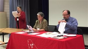 Une femme au micro et deux autres personnes assises derrière une table portant le logo du RSFS.