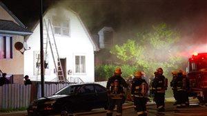 Des pompiers observent une maison en feu.