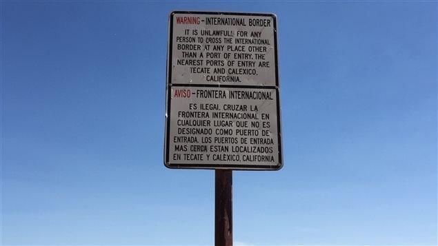 Un panneau bilingue avertit les gens de ne pas traverser la frontière entre les États-Unis et le Mexique, sauf aux postes frontaliers.