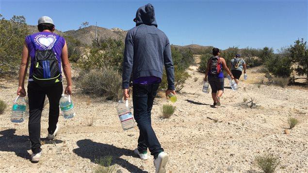 Des bénévoles des Anges de la frontière déposent des bouteilles d'eau pour aider ceux qui doivent survivre dans le désert après avoir franchi le mur.