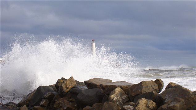 Le phare de Cap-des-Rosiers derrière une vague lors d'une tempête.