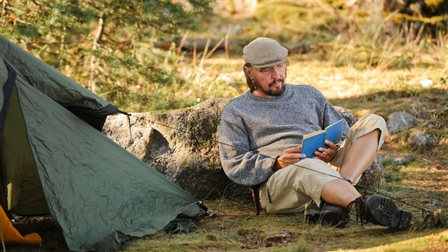 Un homme savoure un livre en forêt.