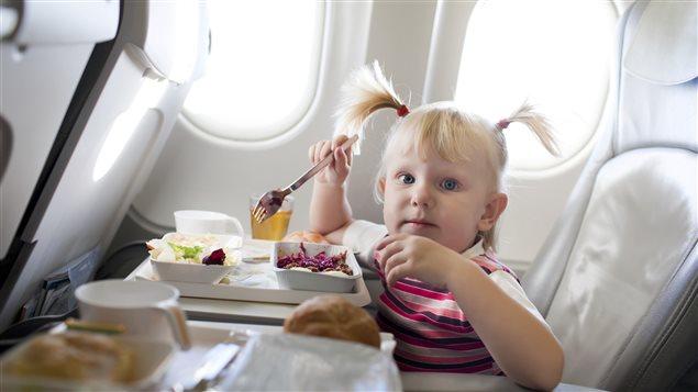 Une fillette mange dans un avion.