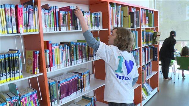 Un garçon consulte un livre dans une bibliothèque
