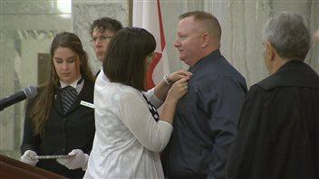 La députée Nicole Goehring remet le ruban de couleur sarcelle à Dan Matheson.