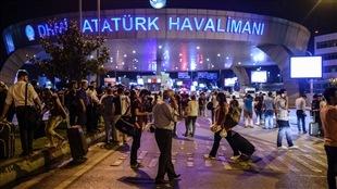 Plusieurs voyageurs attendent près de l'entrée de l'aéroport d'Istanbul après que des attentats-suicides y soient survenus.