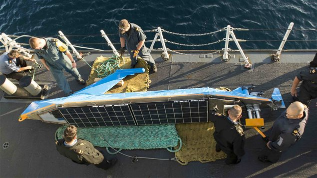 Des marins du NCSM St. John's sortent le Solar Voyager de l'eau.
