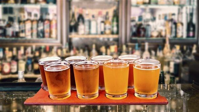 Des bières artisanales sur un comptoir devant des réfrigérateurs pleins de bouteilles.