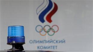 Une lumière stroboscopique bleue, sur le toît d'une voiture devant le drapeau du comité olympique russe, au bâtiment de son siège social à Moscou, en Russie