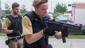 Des policiers armés de mitraillettes arrivent au centre commercial Olympia, à la suite de la fusillade mortelle.